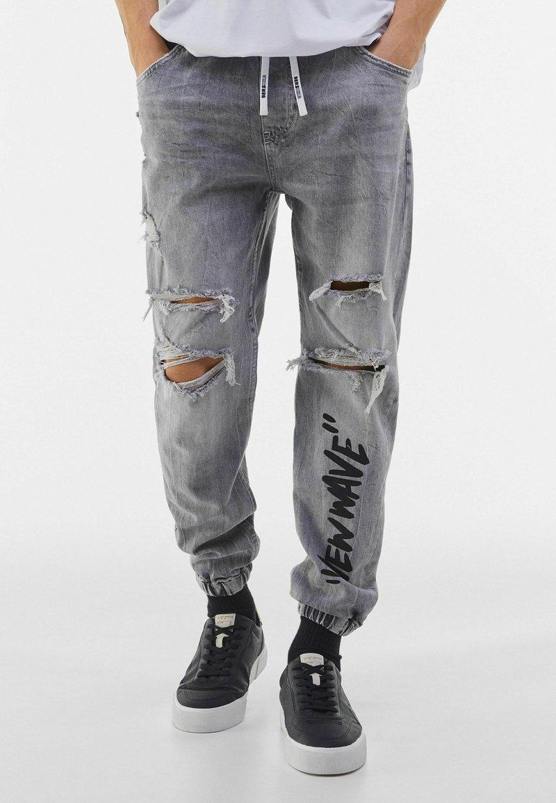 Bershka - MIT PRINT UND ZIERRISSEN  - Jeans Tapered Fit - grey