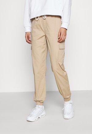 ONLTANJA MAJA STRING - Trousers - beige