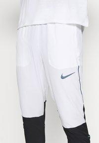 Nike Performance - SWIFT PANT - Träningsbyxor - white/black - 4
