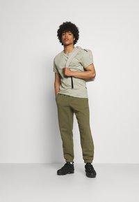adidas Originals - BASICS UNISEX - Spodnie treningowe - olive cargo - 1
