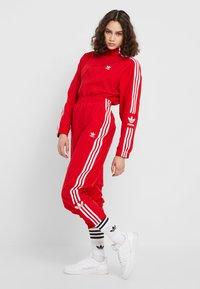 adidas Originals - LOCK UP ADICOLOR NYLON TRACK PANTS - Pantalones deportivos - red - 1