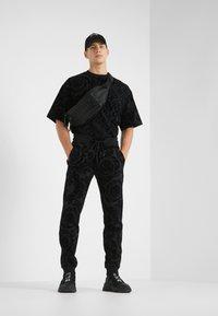 Versace Jeans Couture - BAROQUE JOGGERS - Verryttelyhousut - black - 1