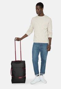 Eastpak - TRANVERZ M - Wheeled suitcase - blakoutstripred - 2