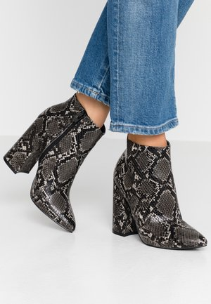High heeled ankle boots - black/white