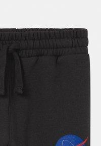 Cotton On - NASA LICENSE SLOUCH  - Teplákové kalhoty - black - 2