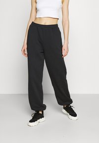 NA-KD - NA-KD X ZALANDO EXCLUSIVE - LOOSE FIT PANTS - Tracksuit bottoms - black - 0