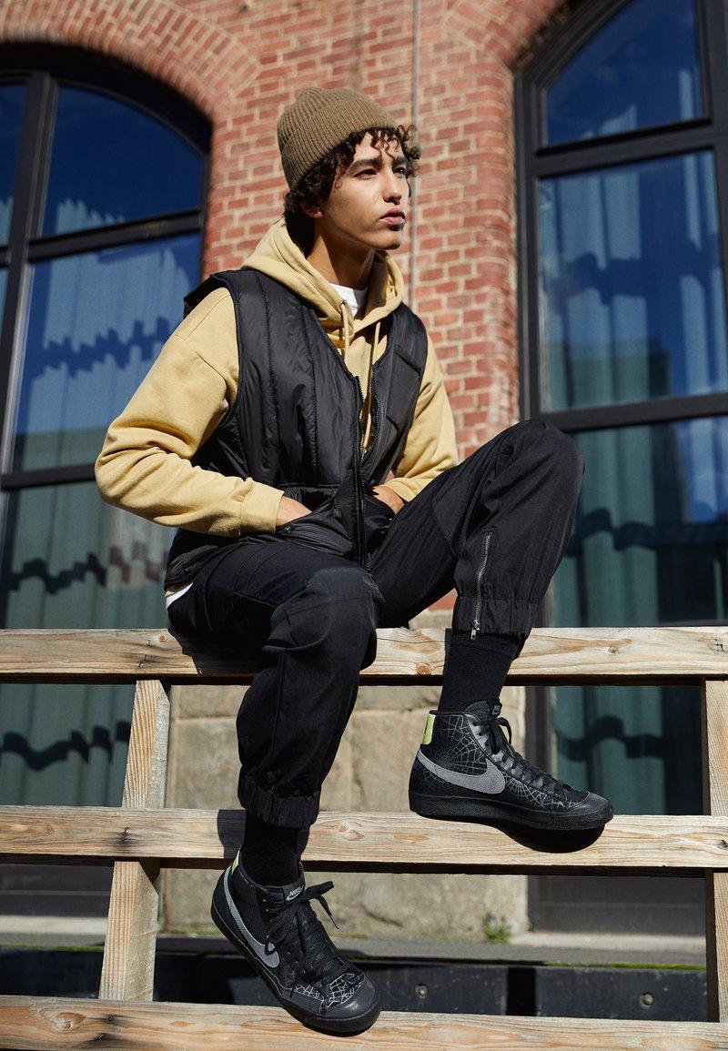 Nike Sportswear - BLAZER MID '77 UNISEX - Zapatillas altas - black/universe gold/metallic silver/sail/white