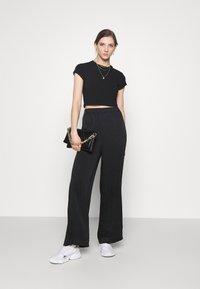 NA-KD - MATIAMU BY SOFIA X STRUCTURED WIDE LEG PANTS - Trousers - black - 1