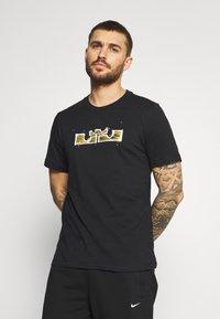 Nike Performance - DRY LOGO TEE - Print T-shirt - black/gold dart - 2