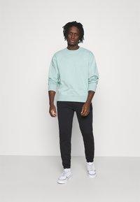 adidas Originals - PANT UNISEX - Tracksuit bottoms - black - 1