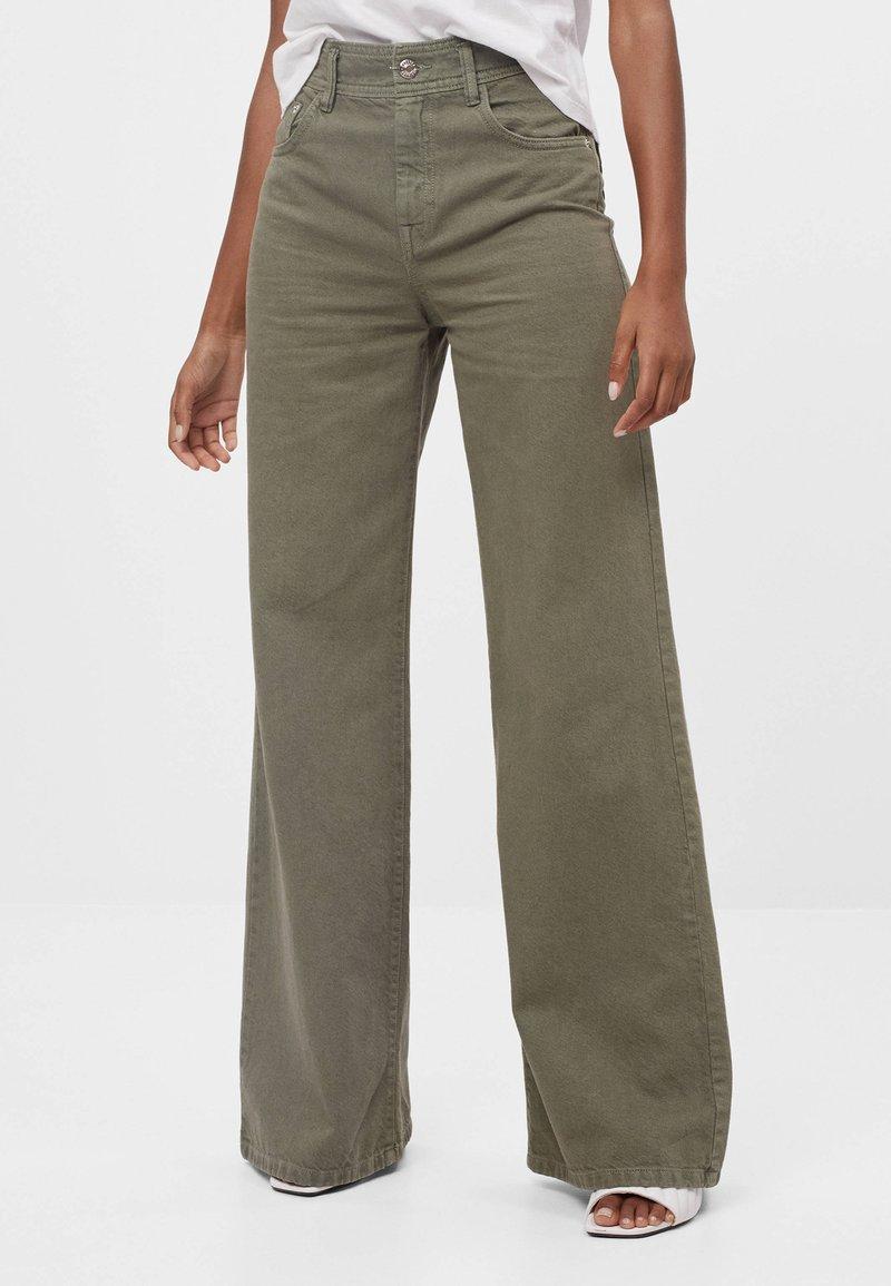 Bershka - MIT WEITEM BEIN - Flared Jeans - green