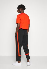 adidas Originals - WARMUP - Tracksuit bottoms - black/corang - 2