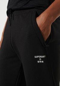 Superdry - Tracksuit bottoms - black - 2