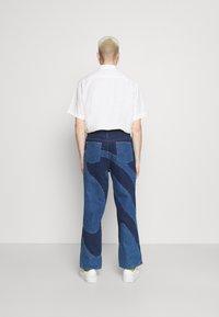 Jaded London - JADED MEN X CURLYFRYSFEED SWIRL CUT & SEW  - Bootcut jeans - dark blue - 2