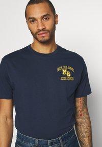 New Balance - ATHLETICS VARSITY TEE - Print T-shirt - dark blue - 3