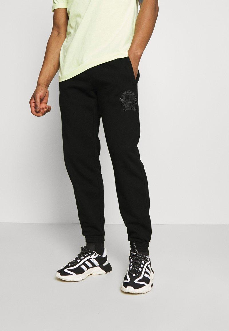 adidas Originals - COLLEGIATE CREST UNISEX - Tracksuit bottoms - black