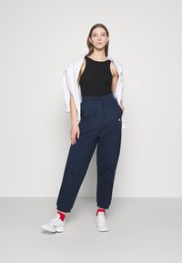 Tommy Jeans - RELAXED BADGE PANT - Tracksuit bottoms - twilight navy - 1