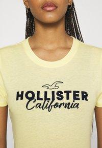 Hollister Co. - TECH CORE - Triko spotiskem - light soft yellow - 4