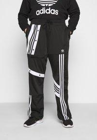 adidas Originals - CATHARI - Tracksuit bottoms - black - 0