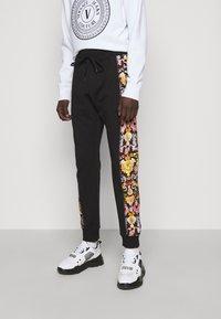 Versace Jeans Couture - HEAVY PRINT VERSAILLES - Tracksuit bottoms - black - 0