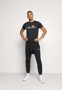 Ellesse - OSTERIA - Tracksuit bottoms - black - 1