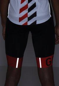 Gore Wear - C5 OPTILINE KURZE TRÄGERHOSE - Punčochy - black/red - 7