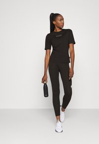Puma - MODERN BASICS TEE - Print T-shirt - black - 1