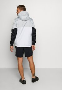 Under Armour - FIELD HOUSE JACKET - Waterproof jacket - white/black - 2