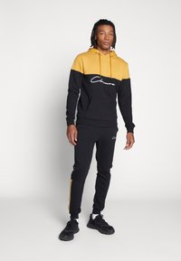 CLOSURE London - CONTRAST SCRIPT JOGGER - Tracksuit bottoms - black/mustard - 1