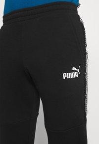 Puma - AMPLIFIED PANTS - Pantalon de survêtement - black - 4