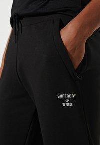 Superdry - Tracksuit bottoms - black - 0