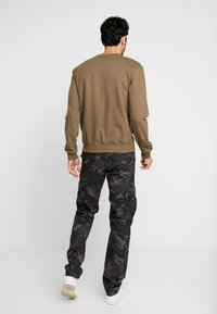 Alpha Industries - Cargo trousers - black camo - 2