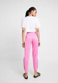 Nike Sportswear - JOGGER LOGO TAPE - Pantalon de survêtement - china rose/black - 3