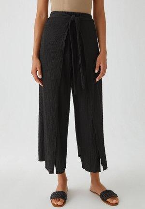 IM PAREO-STIL MIT GÜRTEL - Spodnie materiałowe - black