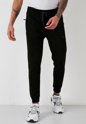 SLIM FIT - Tracksuit bottoms - black