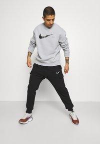 Nike Sportswear - ZIGZAG CARGO PANT - Verryttelyhousut - black - 3