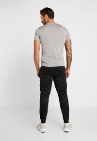 Nike Performance - THRMA TAPER - Pantalon de survêtement - black/mtlc hematite