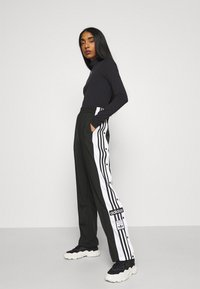 adidas Originals - ADIBREAK - Tracksuit bottoms - black - 1