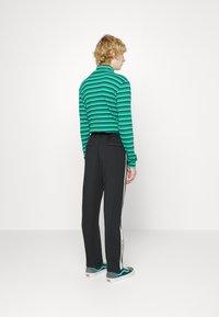 Pegador - WIDE TRACKPANTS UNISEX - Pantalon de survêtement - black/mint - 3