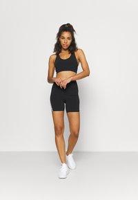 Cotton On Body - V NECK CUT OUT CROP - Light support sports bra - black - 1