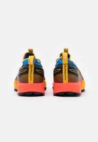 ASICS - FUJITRABUCO PRO - Trail running shoes - black/saffron - 2