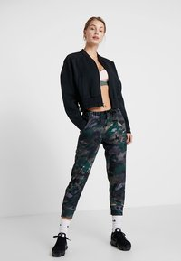 Nike Performance - REBEL ALL IN 7/8 - Tracksuit bottoms - club gold/white - 1