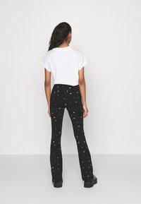 Colourful Rebel - STAR EYE PRINT BASIC FLARE PANTS - Trousers - black - 0
