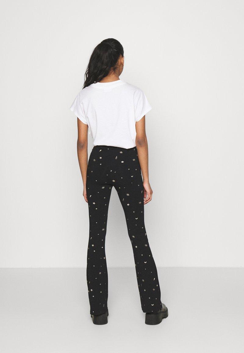 Colourful Rebel - STAR EYE PRINT BASIC FLARE PANTS - Trousers - black