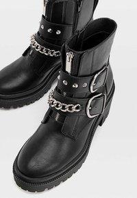 Stradivarius - MIT PROFIL, UND DEKORATIVER KET - Cowboy/biker ankle boot - black - 4