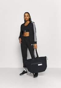 adidas Performance - ESSENTIALS FRENCH TERRY STRIPES PANTS - Pantaloni sportivi - black/white