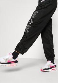 Nike Sportswear - AIR - Tracksuit bottoms - black/white - 4