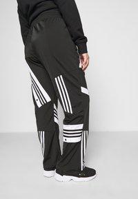 adidas Originals - CATHARI - Tracksuit bottoms - black - 5