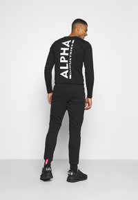 Alpha Industries - BASIC JOGGER FOIL - Tracksuit bottoms - black/yellow gold - 2