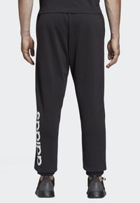 adidas Performance - ESSENTIALS LINEAR TAPERED PANTS - Tracksuit bottoms - black - 1